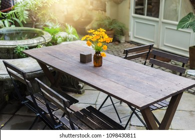Dining wooden table in the outdoor garden decorated with yellow flower vases.