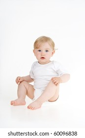 Dinky little girl sitting on white background.