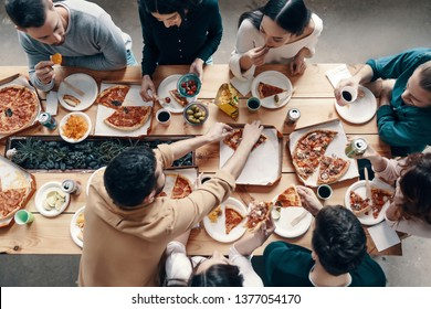 Dinner among friends. Top view of young people in casual wear picking pizza while having a dinner party indoors
