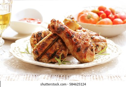 Dinner background. Grilled chicken drumsticks with rosemary.
