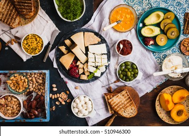 Dinner board with cheese, fruits and wine. Overhead of Cheeses and fruit served on a slate platter.