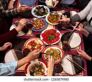 Dinner with friends at the table. View from above. Chinese food with chopsticks.