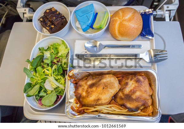 A dinner inflight meal with pasta, chicken, cheese , butter, chocolate dessert and bread on a tray onboard a long flight from Europe to America in economy class.