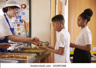 Dinner lady serving kids in a school cafeteria, side view
