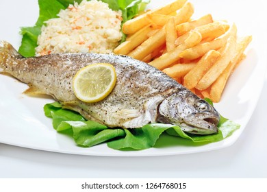 Dinner meal with trout fish, chips and vegetable salad. Big portion on white background.