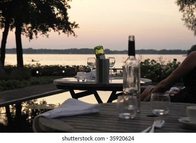 dinner on an outdoor terrace with sunset on a lake and empty bottles of wine