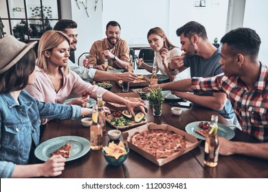 Dinner is on the table. Group of young people in casual wear eating and smiling while having a dinner party