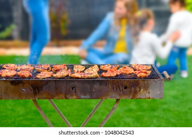 Dinner party, barbecue on back yard. Close-up on chicken fillet on a grill. At background happy kids play.