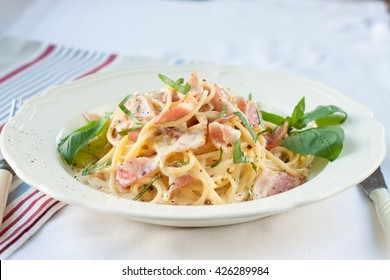 Dinner. Pasta carbonara served on deep plate decorated with basil leaves