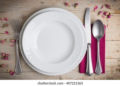 Dinner place setting - two plates of white porcelain, fork, spoon and knife on white, old, wooden table