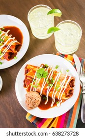 Dinner plate with Chicken enchiladas garnished with green onions and sour cream.