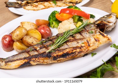 a dinner plate filled with a grilled whole head on branzino fish filets and assorted vegetables in a restaurant setting