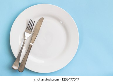 Dinner plate, knife and fork isolated on blue backgroud