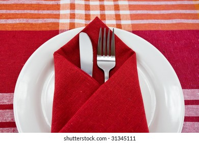 Dinner Plate, Knife, and Fork on the red background