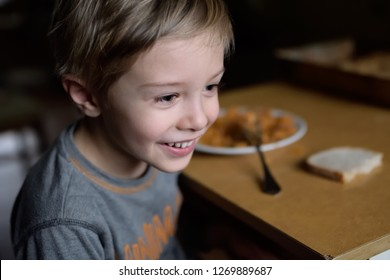 Dinner in a poor family. Food for a poor child. The problem of poverty and lack of food in the world. Poor but happy child.