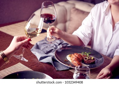 Dinner in a restaurant. 2 woman eating and drinking red and white wine . Atmosphere, happy, festive. hands holdong glasses