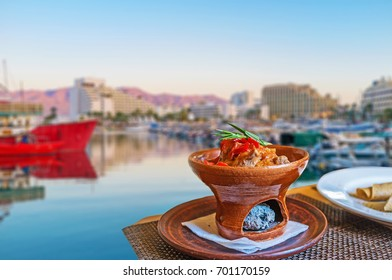 The dinner in restaurant of marina on sunset - the Eastern style beef in a dish with burner, Eilat, Israel.