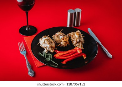 Dinner at the restaurant. Served meat dish with paprika and salad on a black plate with a glass of wine on a red table