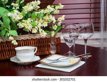 dinner set, coffee mug and jasmine flowers on a background of wicker baskets. interior, wooden table.