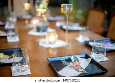 Dinner set on the wood table with long wine glass ware.