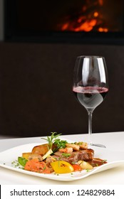 A dinner setting: Delicious juicy barbecued steak and prawns Surf and Turf with grilled tomato and roasted potatoes and a glass of good red wine