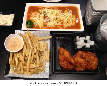 Dinner with spicy chicken wings and french fries cheese