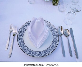 The dinner table for customer. There are spoons, folks, white napkin and grass on the white table.