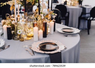 Dinner table decorated by candles and flowers. Wedding. Decor