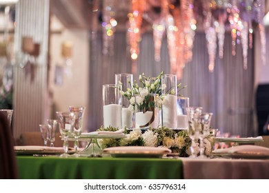 Dinner table decorated with white flowers and candles