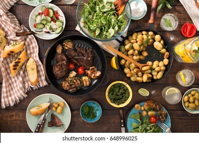 Dinner table with grilled steak, grilled vegetables, potatoes, salad, different snacks and homemade lemonade, overhead view