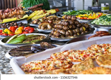 Dinner table with meat grill, roast new potatoes, vegetables, salads, sauces, snacks and lemonadeá Grilled sausage, mushrooms. Stock Photo