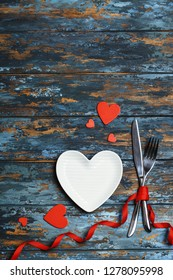 Dinner table with plate. Love concept for mother's day and valentine's day. Valentine. Love postcard. Happy Valentine's day hearts on wooden background. Valentine card with space for text