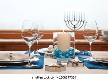 Dinner table setting decorated for Hanukkah Chanukah. Traditional Jewish holidays home celebrations decor.