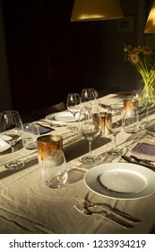 Dinner table setting showing place setting with sunshine, glasses and flowers
