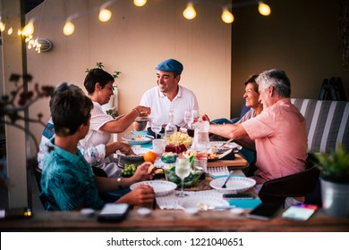 Dinner time in friendship with different ages people all together having fun and enjoying the night with smiles and happiness. Mobile phones defocused in for technology modern concept