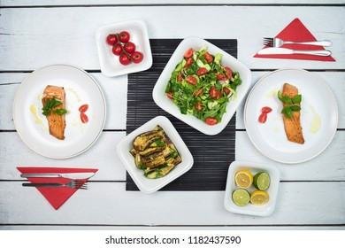 Dinner for two, salmon fish with vegetable salad. Top view on table setting with delicious food on white rustic table.