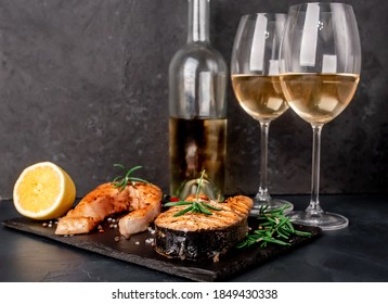 Dinner for two. Salmon steaks, a bottle of white wine and glasses on a stone background. - Shutterstock ID 1849430338