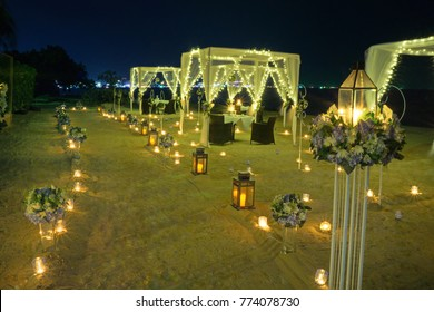 Dinner is under candlelight at the beach.Candlelight is on the beach.Walk on the sand.Gala dinner under candle light by the sea.