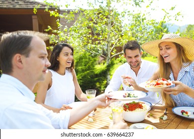 Dinner variety of Italian dishes and lemonade on wooden table in the garden