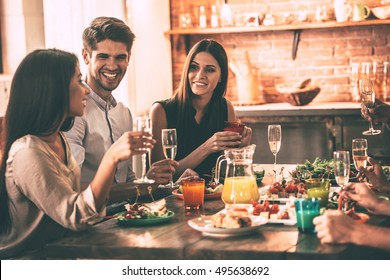 Dinning with friends. Cheerful young people enjoying meal while sitting at the dinning table on the kitchen together