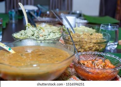 Dinning table with bowls of Kerala vegetable curries like sambar, aviyal, achar,koottu curry serving during Onam and Vishu sadhya