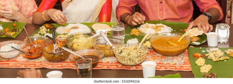 Dinning table with rice and curries serving serving during Onam and Vishu sadhya. Bowls of Kerala vegetable curries like sambar, aviyal, achar,koottu curry