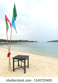 Dinning table is set on the white beach and calm ocean for the evening dinner restaurant decorated with 3 different color flags of green red and blue, common seen on the tourist island or beach resort