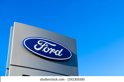 Dinslaken, Germany - December 18. 2019: Isolated blue silver logo lettering of american automobile manufacturer Ford against cloudless blue sky