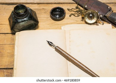 The dip pen and old book on the wood table