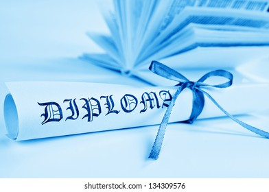 Diploma with blue ribbon and book