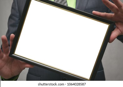 Diploma certificate of best worker or manager mock up. Businessman holding in hands a blank photo frame isolated on gray background. Close up photo.