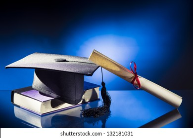 Diploma, Graduation hat and book on a blue background