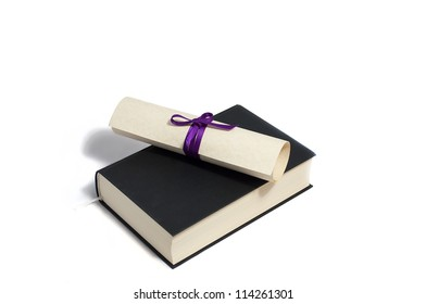 diploma with purple bow on black book isolated on white