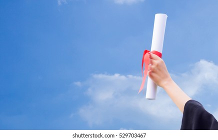 Diploma with a red ribbon in hand on sky background